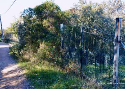 Overwoekerd ijzeren hek langs wandelroute Cerro da Goldra