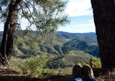 Voeten van zittende wandelaar onder Pinheiro met uitzicht over groene heuvels Oost-Algarve