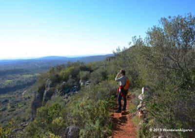 Wandelaar op de rotswand van Rocha da Pena, wandelroute Loulé