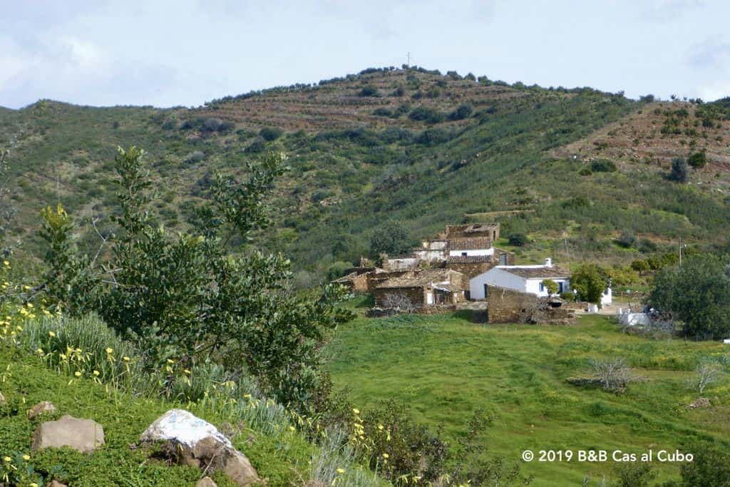 Ruines en één bewoond huis tegen een groene heuvel
